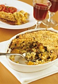 Pasta bake with pumpkin in the baking dish; red wine