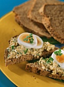 Linseed bread with egg spread on yellow plate