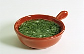 Herb sauce in a red china dish