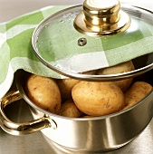 Potatoes in stainless steel pan with glass lid & fabric napkin
