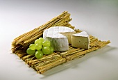 Camembert with piece cut out on straw mat; grapes