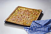 Leek and onion quiche with peanuts on baking tray