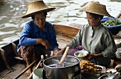 Thai women cooking soup on a boat