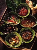 Spicy sauces in banana leaf bowls on tray
