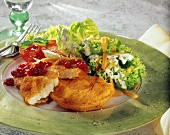 Breaded fish fillet with salad leaves and cranberries