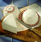 Ricotta, packed and unpacked, with knife on wooden board