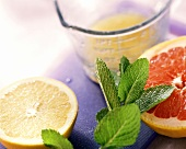 Grapefruit halves & grapefruit juice in measuring jug; mint