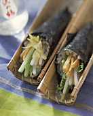 Sushi rolls with vegetables in bamboo bowls