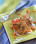 Curried veal fillet with tomato yoghurt on green plate