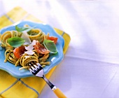 Spaghetti with herb pesto and tomatoes on blue plate