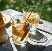 White sangria in glasses on table in open air