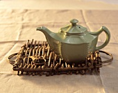 Green teapot on a wooden tray with a spoonful of tea leaves