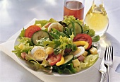 Salad leaves with ham, egg & cheese on plate; oil, vinegar