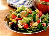 Salad leaves with ham on plate, sieve with tomatoes beside it