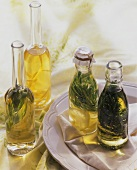 Three bottles of herb oil and a bottle of lemon oil