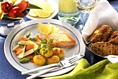 Salmon with fried potatoes, vegetables & lemon wedges; bread