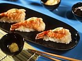 Nigiri with shrimp tails on black platter; chopsticks