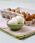 Three shelled boiled eggs, with  eggs in an egg box behind