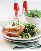 Two turkey slices with green asparagus & beans on plate