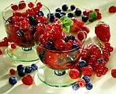 Red berry compote in two bowls, surrounded by fresh berries