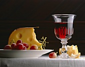 A piece of Emmental cheese, red grapes, red wine and bread