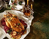 Whole stuffed duck with red cabbage; candles; Christmas décor