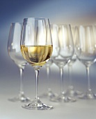A half filled white wine glass in front of empty glasses