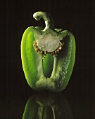 Half a green pepper against a black backdrop