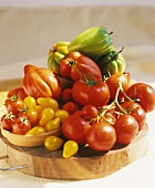 Various types of tomato on a wooden plate