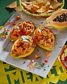 Baked papayas with tomatoes; tortilla chips