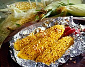 Corn cobs with chili and garlic in aluminium foil