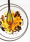 Salad vinaigrette on glass plate with whisk