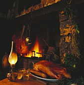 Roast duck on a platter in front of an open fireplace