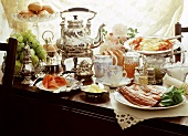 Brunch with fish, raw ham, fruit, pastry and tea