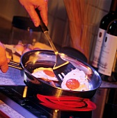 Eggs frying in a pan on a Ceran cooktop