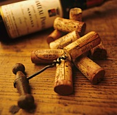 Corks and corkscrews in front of a wine bottle