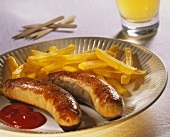 Fried sausages with chips and ketchup on a plate