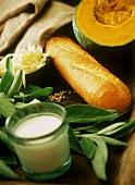 Still life with pumpkin, baguette, cheese, sage & milk