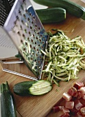 Grated courgettes on wooden chopping board