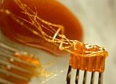 Caramelised sugar, partly on fork
