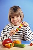 Small girl threading vegetables on skewer