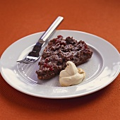 A piece of chocolate cherry cake with blob of cream on plate