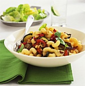 Pasta crescents with roasted vegetables and pine nuts