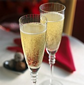 Two champagne glasses on a table in front of red napkin