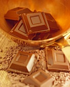 Pieces of chocolate on cocoa powder and in brass bowl