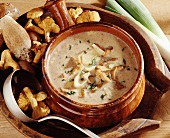 Mushroom soup with leeks in brown ceramic pot