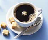 A cup of black coffee with raw cane sugar cubes