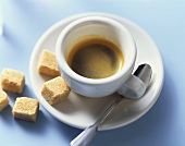A cup of espresso with raw cane sugar cubes