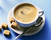 A cup of caffe crema and raw sugar cube