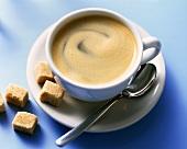 Eine Tasse Caffe Crema und Rohzuckerwürfel